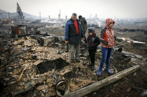 Local residents stand amidst the debris of a burnt building in the settlement of Shyra